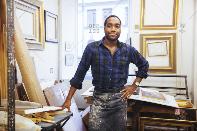 Portrait of smiling young male artist standing with hand on hip at framing workshop