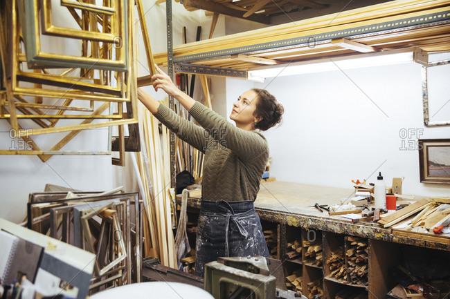 Confident young female artist holding frame at workshop