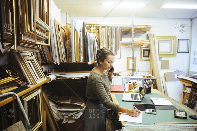 Confident young craftswoman talking on smart phone while writing in paper at workbench in framing store