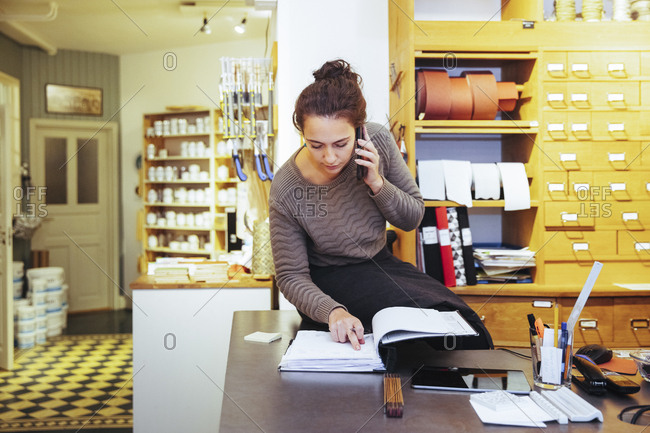 Young saleswoman looking at document while talking on mobile phone sitting in home improvement store