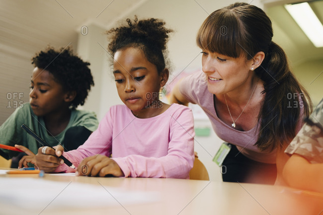 Smiling female teacher looking at students drawing in class