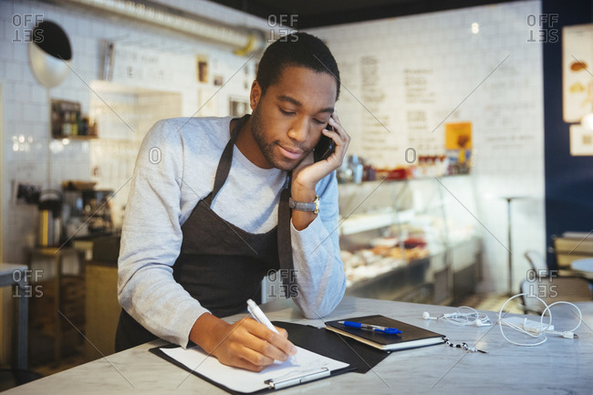 Confident young male employee talking through smart phone while writing on clipboard at delicatessen
