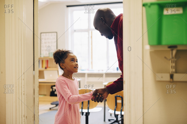 Teacher shaking hand with boy at doorway in classroom