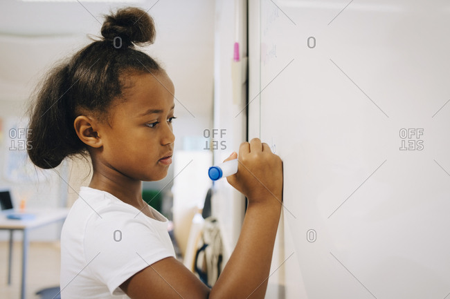 Schoolgirl writing on whiteboard at classroom