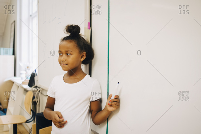 Schoolgirl showing spelling on whiteboard at classroom