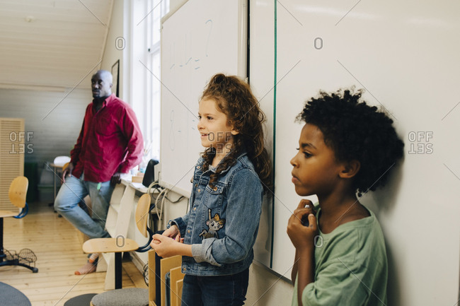 Male and female students standing against whiteboard at elementary school