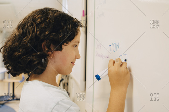 Side view of boy with curly hair writing on whiteboard at classroom