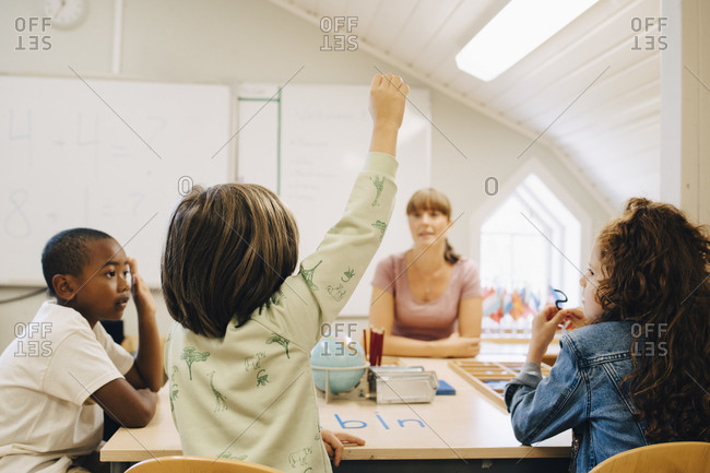 Schoolboy raising hand while answering teacher in classroom at school