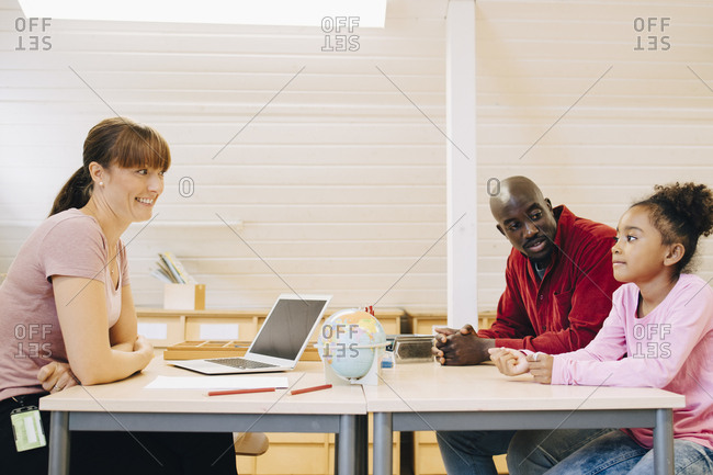 Smiling teacher and man looking at boy during meeting in school