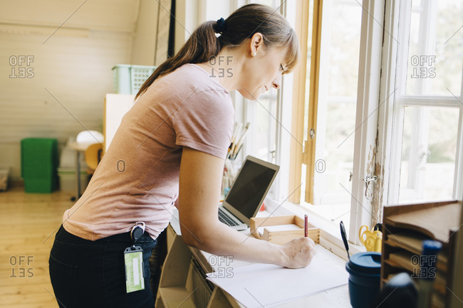 Confident teacher writing on paper while standing by window at classroom in school