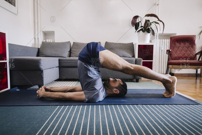 Young adult man practicing yoga in living room at home.
