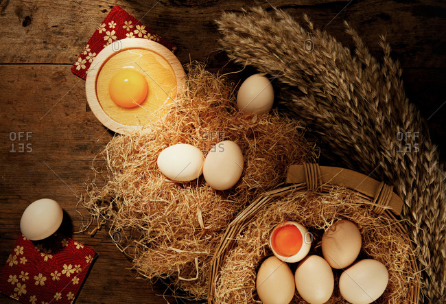 Eggs on wooden table with wheat and straw