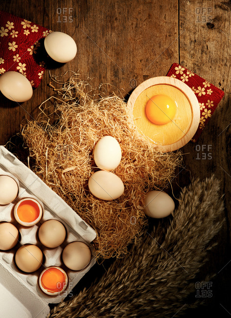 Eggs with carton on wooden table with wheat and straw