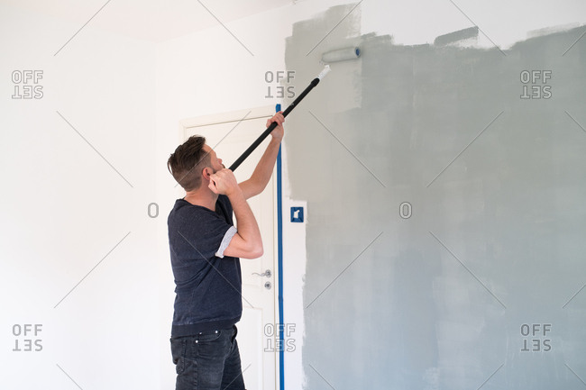 Man painting a room light gray with roller