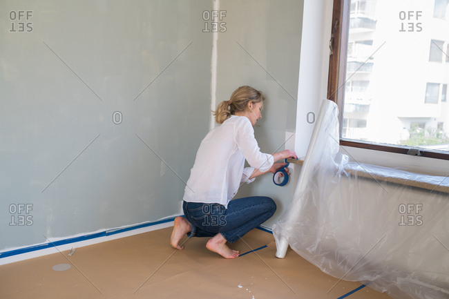 Woman taping around windowsill while painting