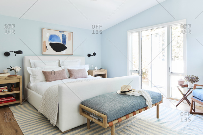 Los Angeles, CA -  January 12, 2019: Comfortable bed in a modern bedroom with light blue walls