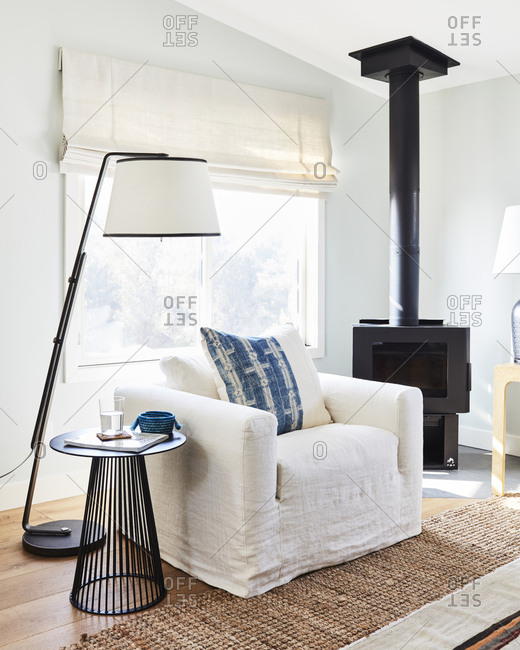 Los Angeles, CA -  January 11, 2019: White cozy chair by wood stove in a modern home