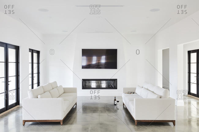 Los Angeles, CA - February 9, 2019: Bright white living room with large tv and fireplace
