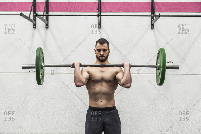 Muscular man without a shirt lifting a barbell at the gym