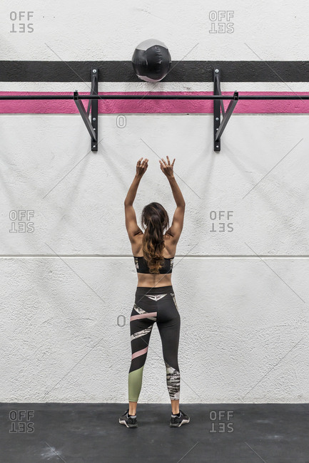 Fit woman throwing a ball against a wall in the gym