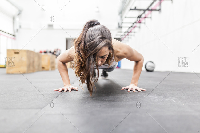Beautiful and young woman does push-ups on the floor at the gym