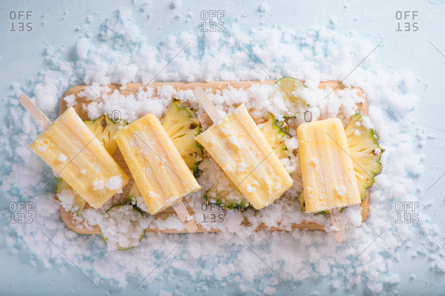 Yellow fruit popsicles on a plate, top view over a blue wood background.