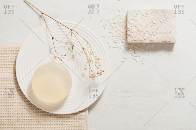 Overhead view of rice milk body soap on a plate with dried flowers