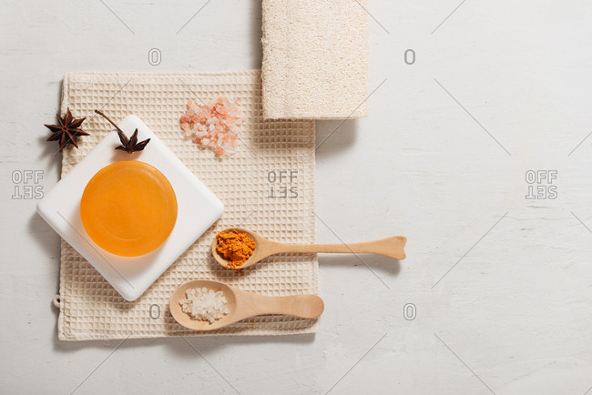 Overhead view of handmade soap with cinnamon, pink salt, and anise star on a spa towel