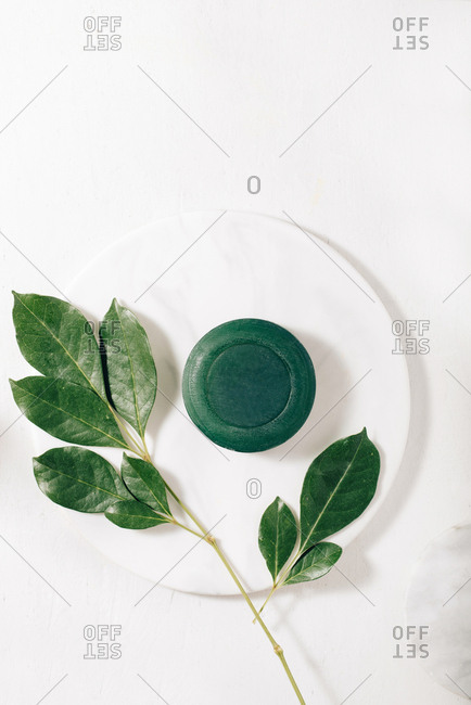 Pieces of natural soap on a white plate with oil and herbs