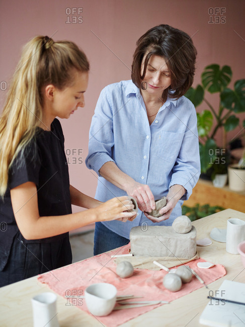 Young ceramic artist teaching mature female student how to form clay bowl during individual class in art studio