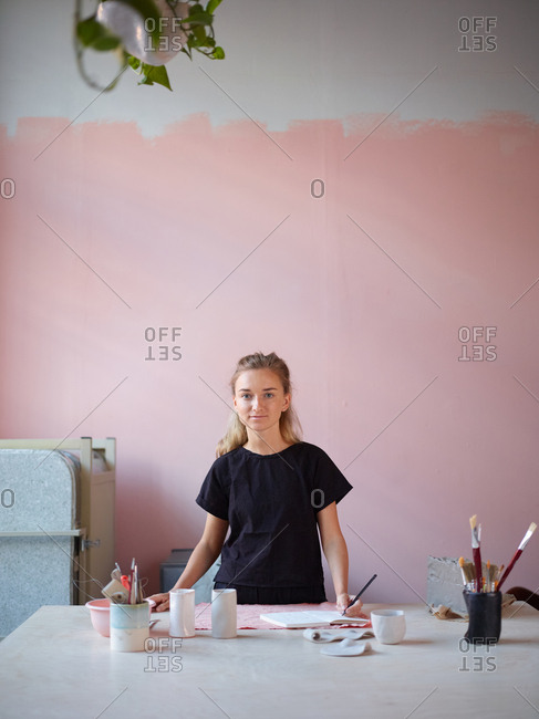 Portrait of young female ceramic artist drawing in sketchbook at desk in her studio and looking at camera