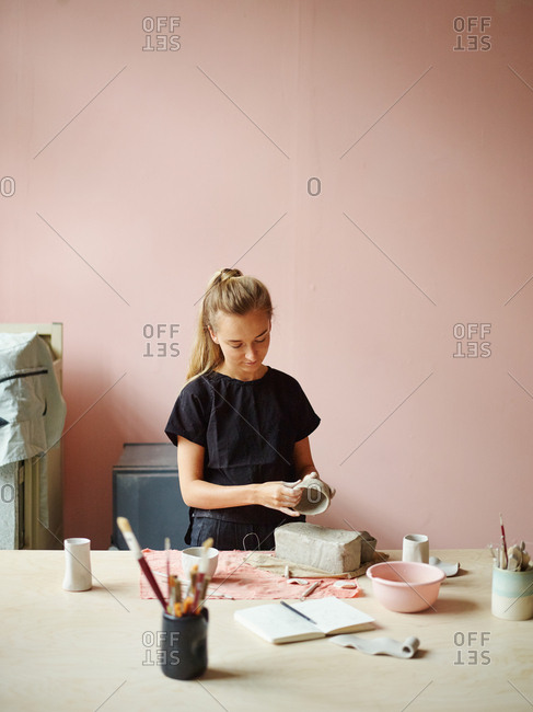 Young female ceramic artist making clay bowl at desk in her studio. Bar of clay, open sketchbook and mugs with brushes in front of her