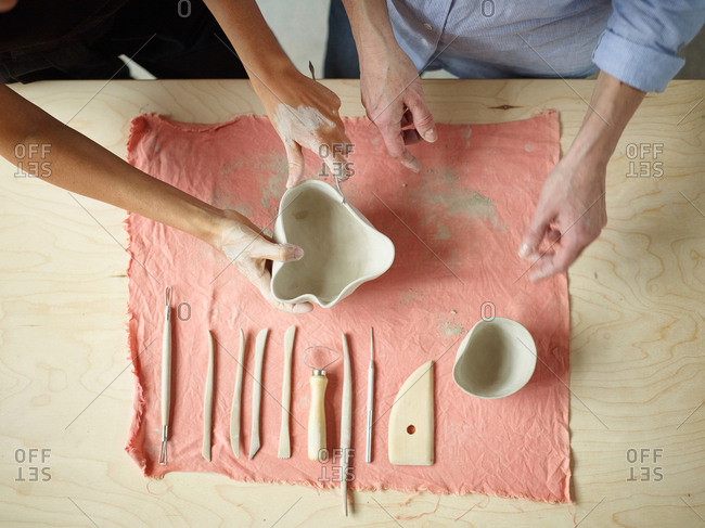 Directly above of female artist teaching adult student how to trim curved edge of unfinished ceramic bowl, set of wooden clay modeling tools in front of them