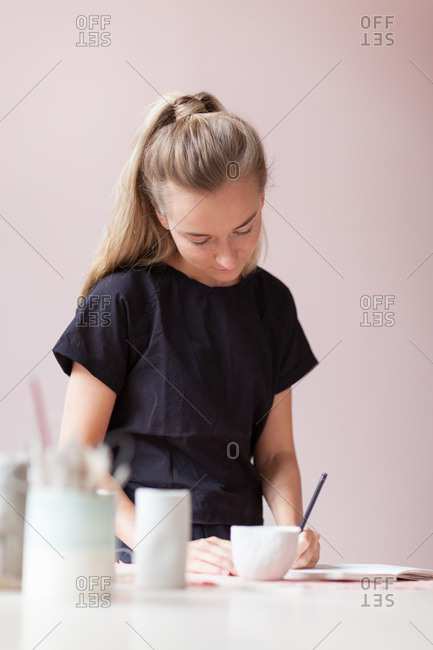 Young female ceramic artist sketching at desk in her studio with light pink walls