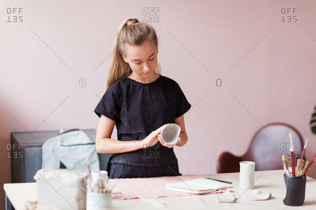 Young female ceramic artist examining carefully unfinished clay bowl at desk in her studio.
