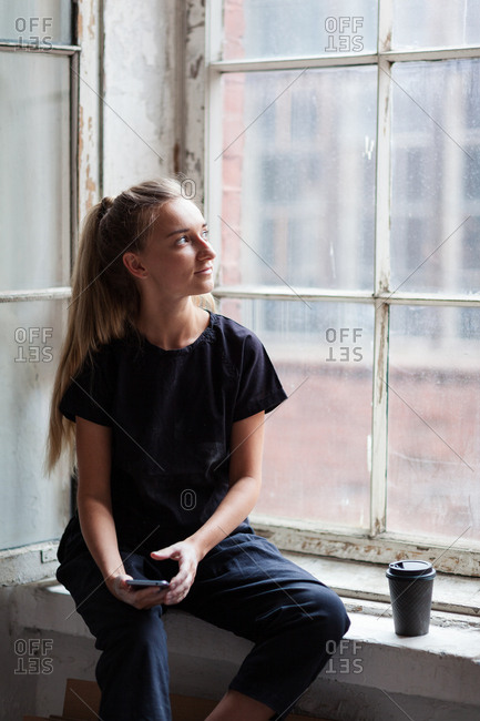 Creative young woman sitting on window sill with cell phone in her hand and looking through old dirty glass dreamily, paper cup of coffee placed nearby