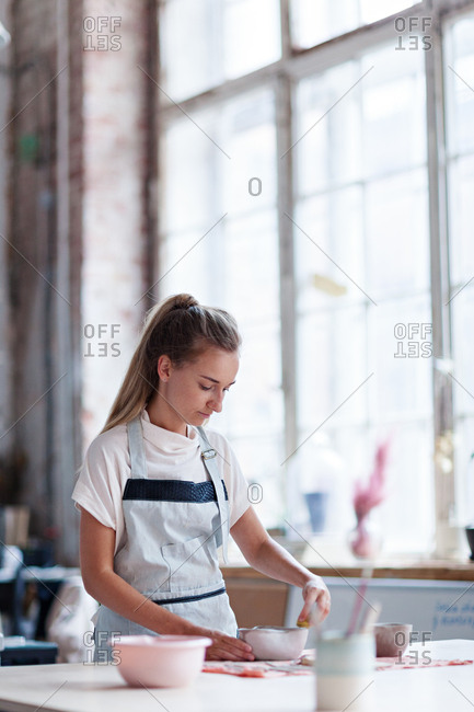 Young female ceramic artist in apron wiping unfinished clay bowl with wet sponge standing at work table in studio