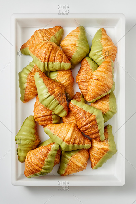 White frame with homemade fresh croissants in a plastic container on a gray background. Continental breakfast concept. Top view.