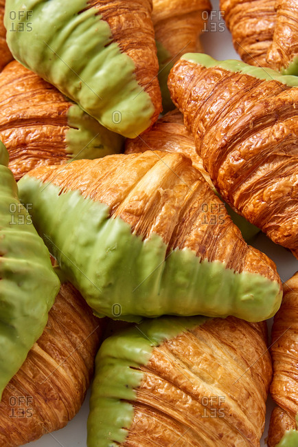 Close up view of homemade delicious French croissants with green sweet icing. Concept of breakfast continental.
