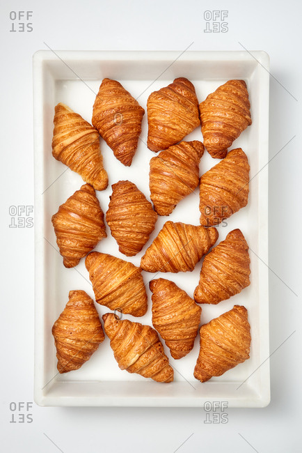 Plastic box with freshly baked pastry homemade tasty croissants on a gray background. Concept of breakfast continental. Top view.