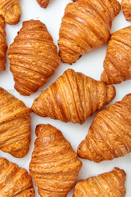 Top view of fresh homemade tasty baked goods, crispy French croissants on a gray background. Concept of continental breakfast.