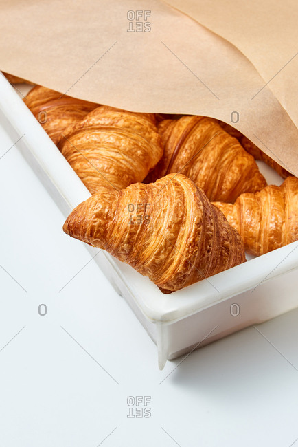 White plastic container with homemade fresh delicious crunchy croissants covered baking paper on a light gray background. Place for text.