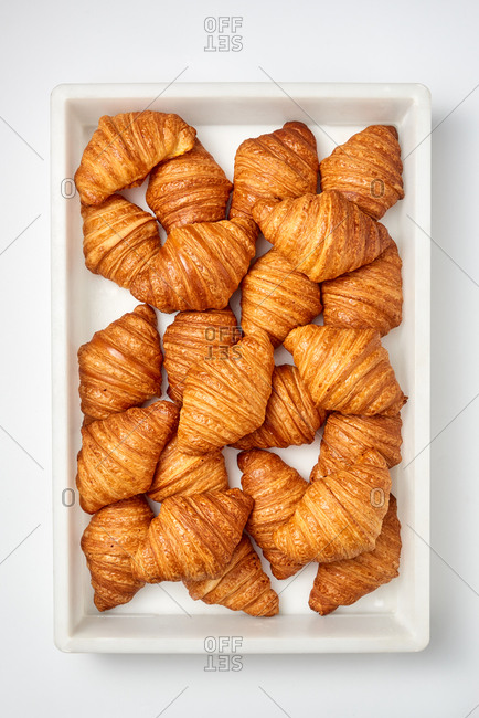 Freshly baked homemade French croissants in a plastic box on a light gray background. Top view. Concept of continental breakfast.