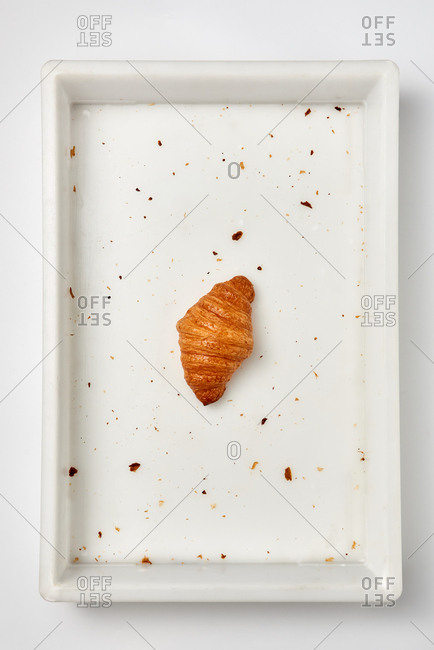 Fresh homemade delicious croissant in a white plastic container with crumbs on a light gray background. Place for text. Top view.