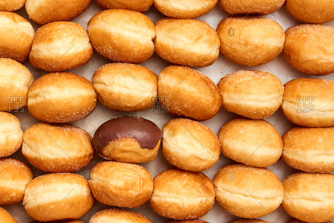 Delicious homemade bakeries fresh doughnuts background with one glazed chocolate. Top view. Food pastry background.