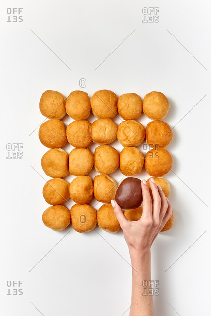 Female's hand puts fresh homemade doughnut with chocolate icing in a dessert baked food pattern square shape on a light gray background. Copy space. Flat lay.