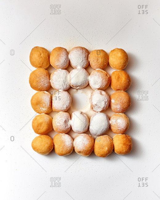 Food pattern of square shape from freshly baked homemade donuts in a sugar powder on a light gray background. Copy space. Top view.