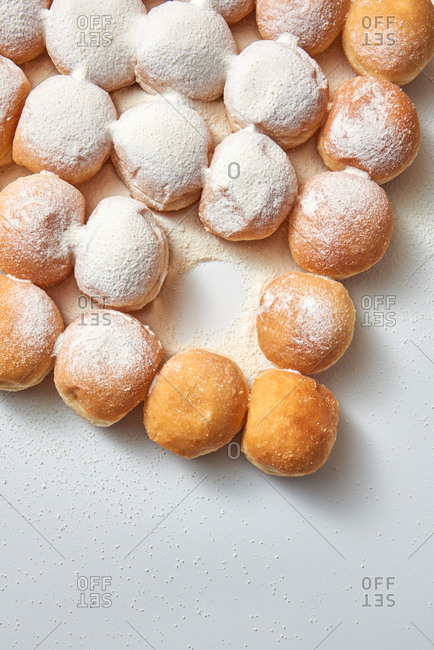 Freshly baked tasty donuts in a powered sugar in a pattern on a light gray background with copy space. Flat lay.