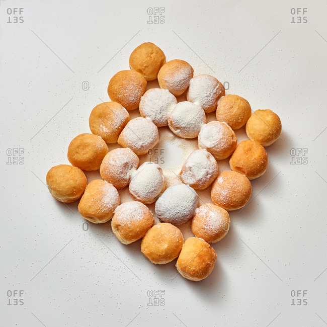 Square food pattern from homemade delicious doughnuts in a sugar powder on a light gray background, place for text.