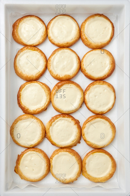Freshly baked homemade small round cakes, vatrushka filled with vanilla cream cottage cheese on a light gray background. Food pattern. Top view.